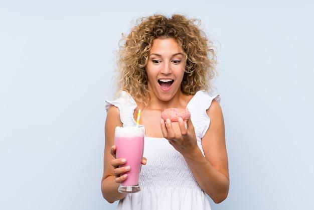 Молодая блондинка с вьющимися волосами держит клубничный молочный коктейль и пончик