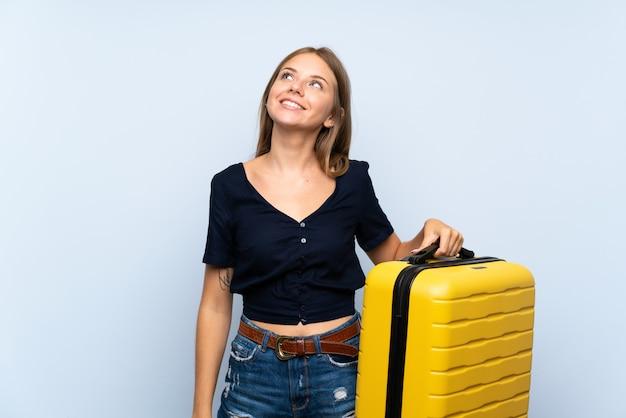 Блондинка путешественник с чемоданом, глядя вверх, улыбаясь