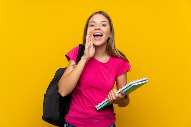Молодая студентка кричит с широко открытым ртом