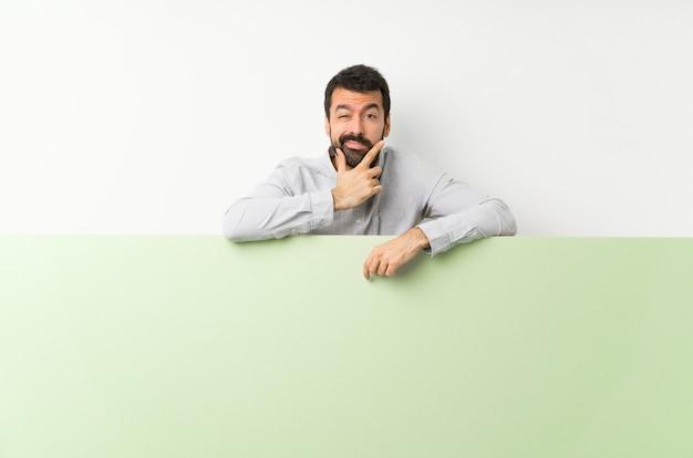 Молодой красивый мужчина с бородой держит большой зеленый пустой плакат мышления