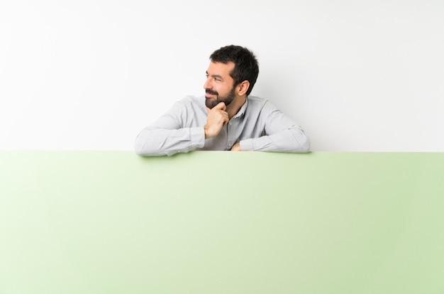 Молодой красавец с бородой, проведение большой зеленый пустой плакат, глядя в сторону