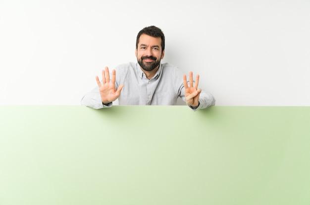 Молодой красивый мужчина с бородой держит большой зеленый пустой плакат, считая восемь с пальцами