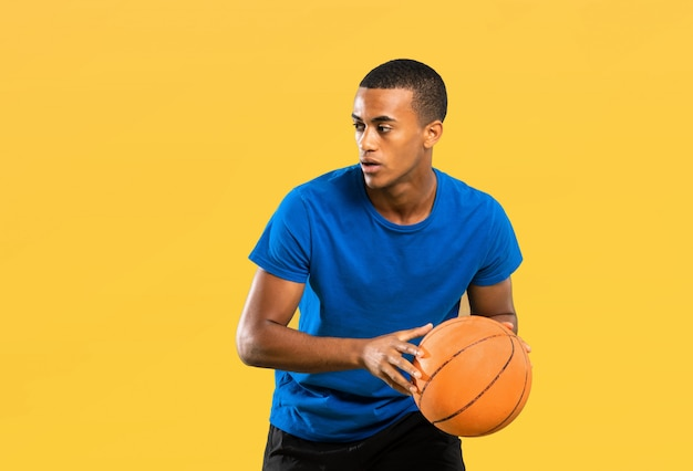 Афро-американский баскетболист человек над желтой стеной