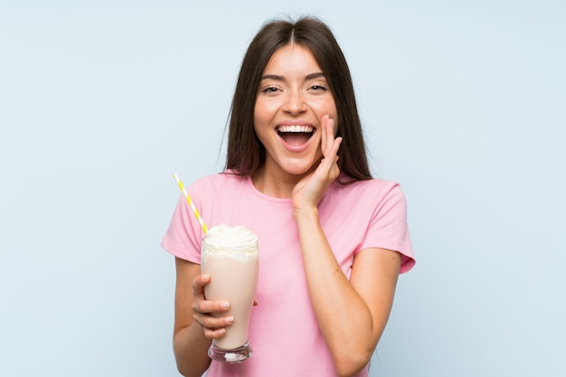 驚きとショックを受けた表情とイチゴのミルクセーキを持つ若い女性