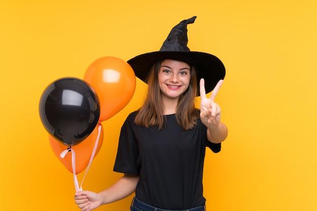 Молодая ведьма держит черные и оранжевые воздушные шарики для вечеринок на хэллоуин, улыбается и показывает знак победы