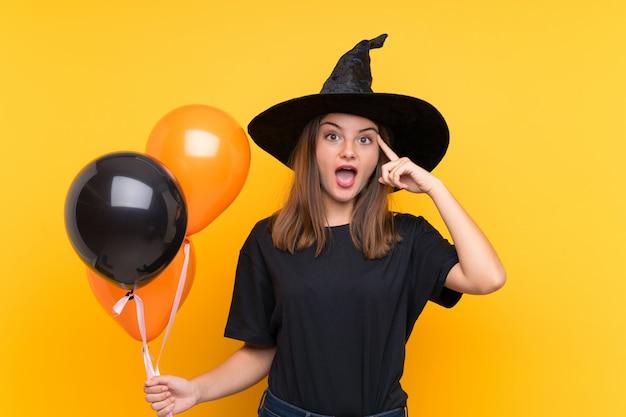 ハロウィーンパーティーの黒とオレンジの気球を保持している若い魔女が解決策を実現しよう