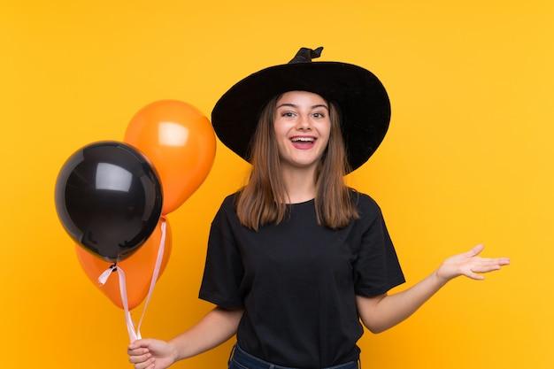 Молодая ведьма держит черные и оранжевые воздушные шарики для вечеринок в хэллоуин с шокированным выражением лица