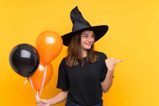 Молодая ведьма держит черные и оранжевые воздушные шарики для вечеринок на хэллоуин, указывая в сторону, чтобы представить продукт