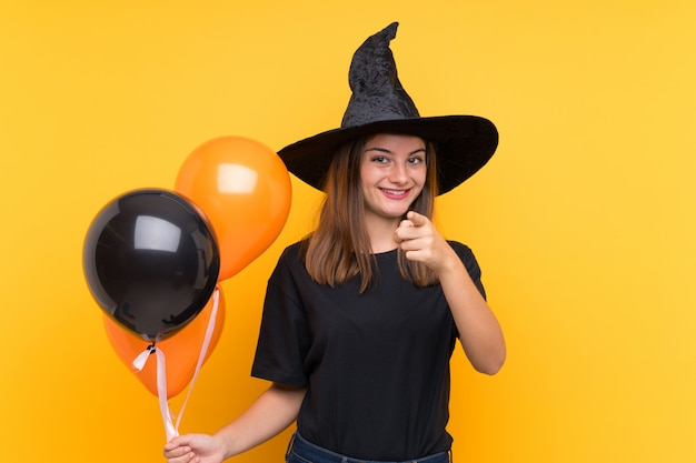 ハロウィーンパーティーの黒とオレンジの気球を保持している若い魔女は自信を持って表現であなたに指を指す