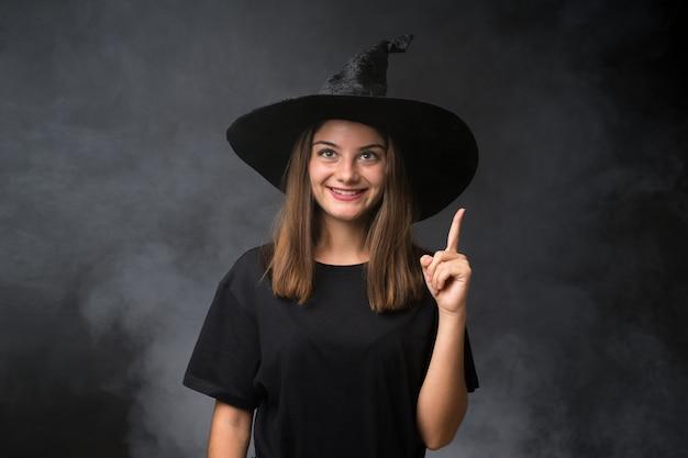 Девушка с костюмом ведьмы для вечеринок хэллоуина над изолированной темной стеной, указывая указательным пальцем отличная идея