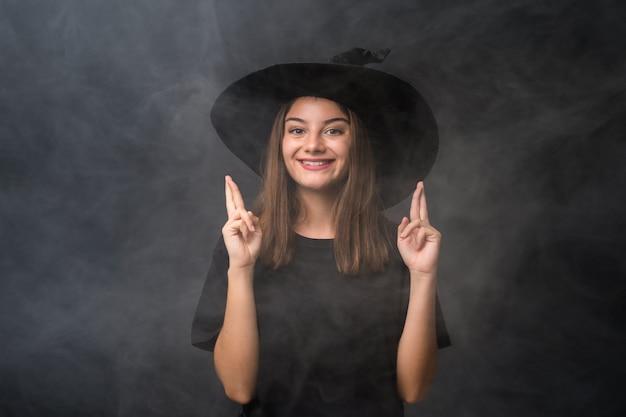 指を交差で孤立した暗い壁の上のハロウィーンパーティーの魔女の衣装を持つ少女