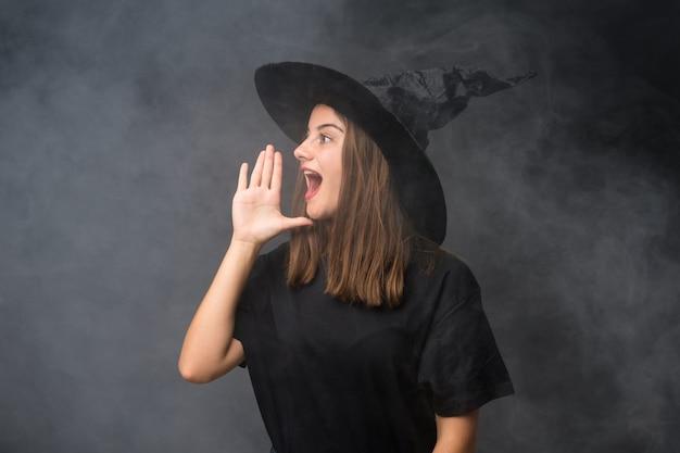 口を大きく開けて叫んで孤立した暗い壁にハロウィーンパーティーの魔女の衣装を持つ少女