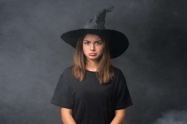 孤立した暗い壁悲しい上のハロウィーンパーティーのための魔女の衣装を持つ少女