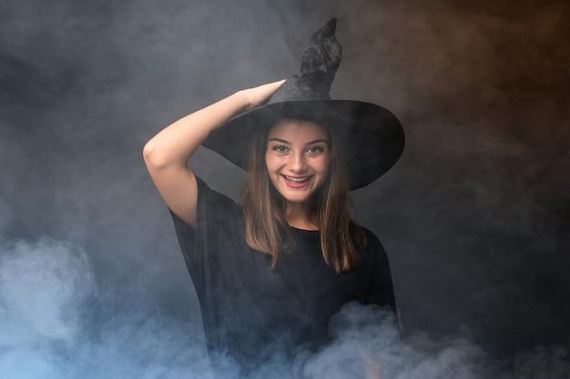 Молодая ведьма держит черные и оранжевые воздушные шарики для вечеринок в честь хэллоуина