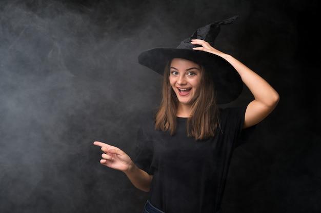驚いたと側に指を指している孤立した暗い壁の上のハロウィーンパーティーの魔女の衣装の女の子