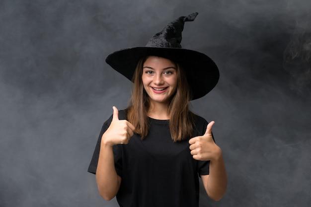 Девушка с костюмом ведьмы для вечеринок хэллоуин над изолированной темной стеной, давая пальцы вверх жест