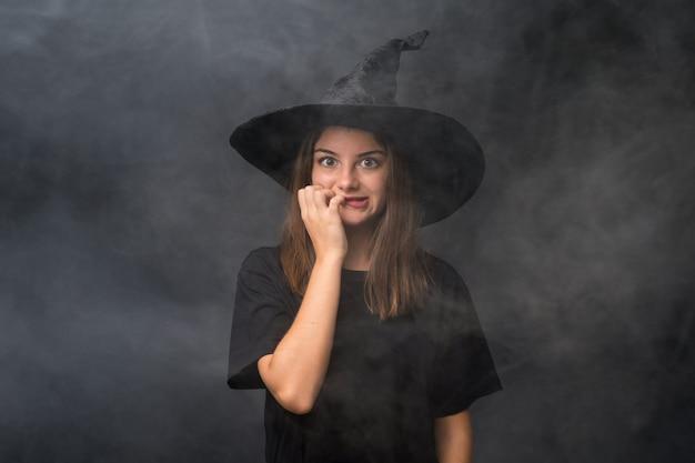 神経質で怖い孤立した暗い壁の上のハロウィーンパーティーの魔女の衣装を持つ少女