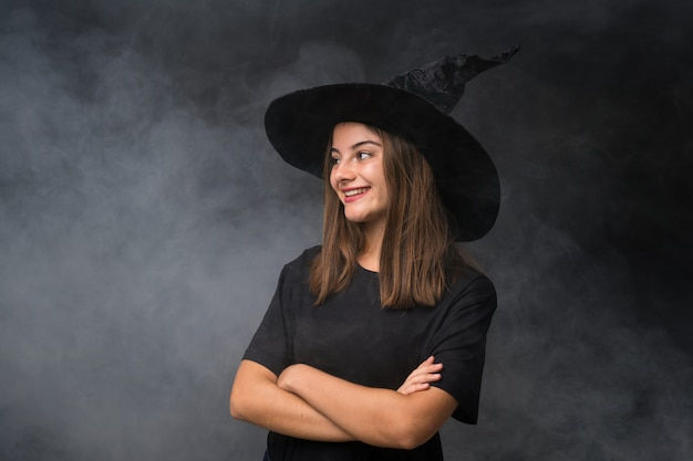 側にいる孤立した暗い壁の上のハロウィーンパーティーの魔女の衣装を持つ少女