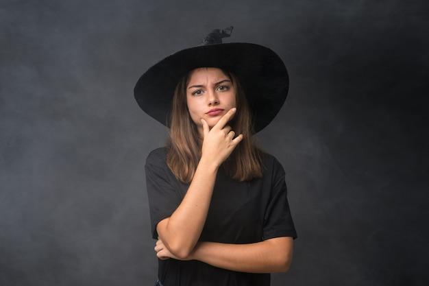 アイデアを考えて孤立した暗い壁の上のハロウィーンパーティーの魔女の衣装を持つ少女