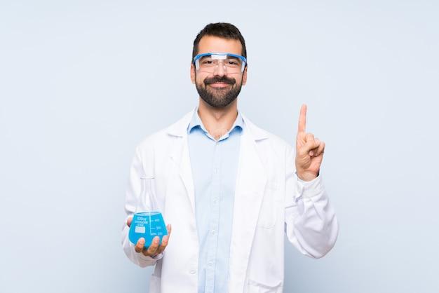 若い科学持株実験室フラスコを示すと最高のサインで指を持ち上げる