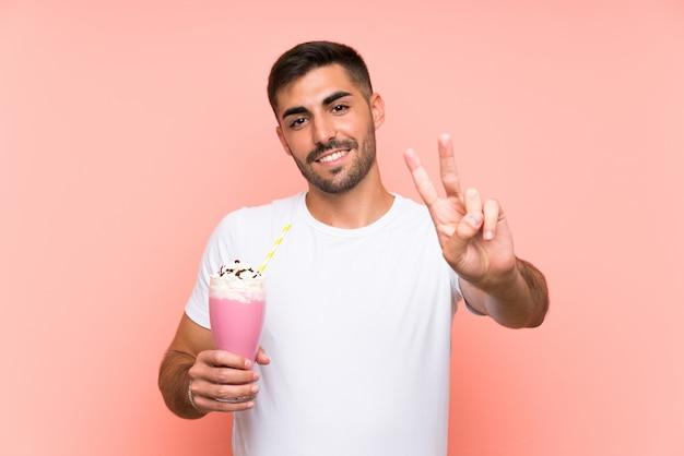 イチゴのミルクセーキ笑顔と勝利のサインを示すと若い男