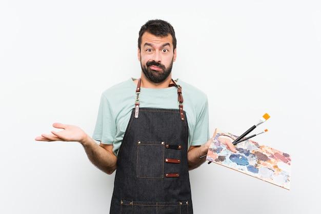 パレットを持って若いアーティスト男が混乱しています。