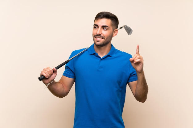 指を持ち上げる若いハンサムなゴルファーの男