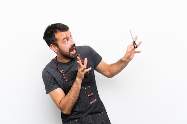 Мужской парикмахер в фартуке нервный и напуганный