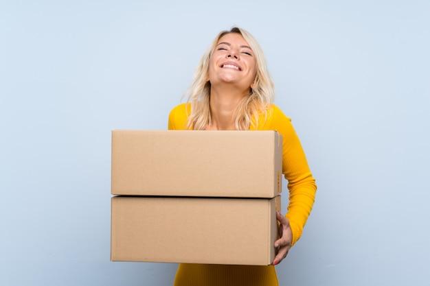 Молодая блондинка держит коробку, чтобы переместить ее на другой сайт