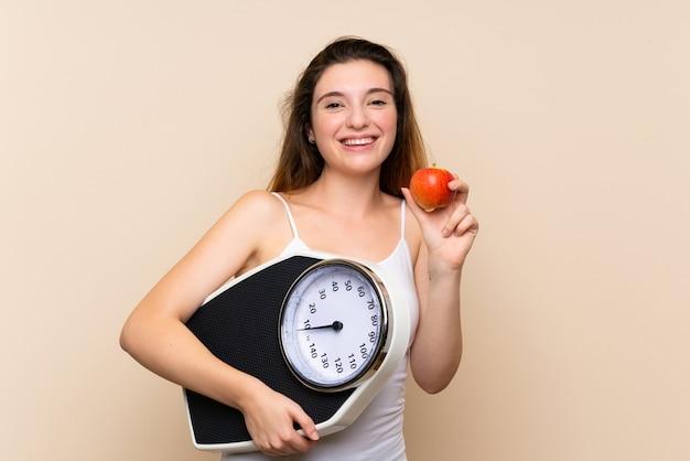 計量機とリンゴの若いブルネットの少女