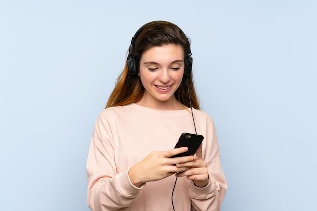 ヘッドフォンで携帯電話を使用して若いブルネットの少女