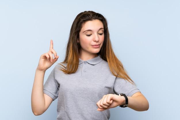 手の時計を見て若いブルネットの少女