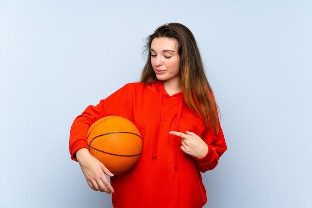 Молодая брюнетка девушка с мячом баскетбола и указывая его