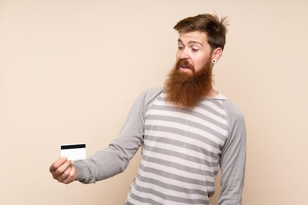 Рыжий мужчина с длинной бородой держит кредитную карту