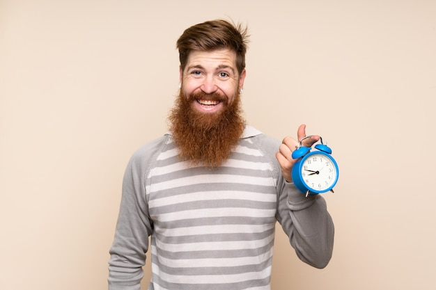 ビンテージ目覚まし時計を保持している長いひげと赤毛の男