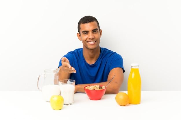 テーブルハンドシェイクで朝食を持っている若い男