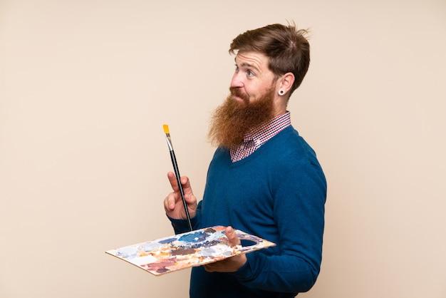 パレットを押しながらアイデアを考えて長いひげを持つ赤毛の男