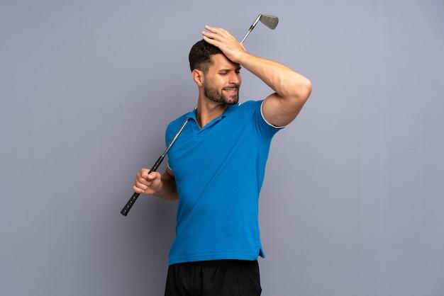ゴルフをしているハンサムな若い男は何かを実現しました
