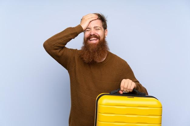 スーツケースを保持している長いひげを持つ赤毛の男は何かを実現し、解決策を意図しています