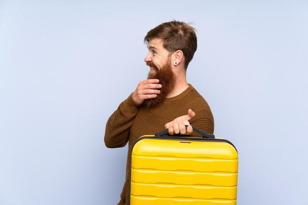 アイデアを考えて、側を見てスーツケースを保持している長いひげを持つ赤毛の男