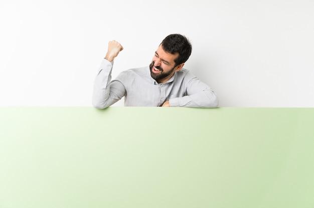 勝利を祝う大きな緑の空のプラカードを保持しているひげの若いハンサムな男