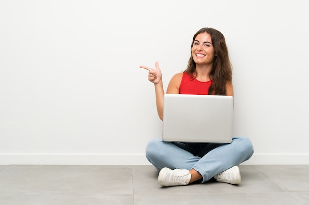 Молодая женщина с ноутбуком сидит на полу, указывая пальцем в сторону