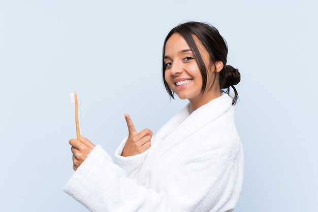 彼女の歯を磨くとそれを指すバスローブで若いブルネットの女性