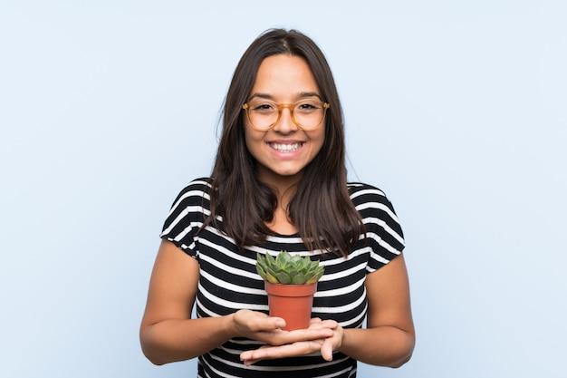植物を保持している若いブルネットの女性