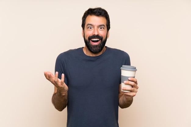 Человек с бородой, держа кофе с шокирован выражением лица