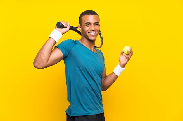 孤立した黄色の壁の上のアフロアメリカンテニスプレーヤー男