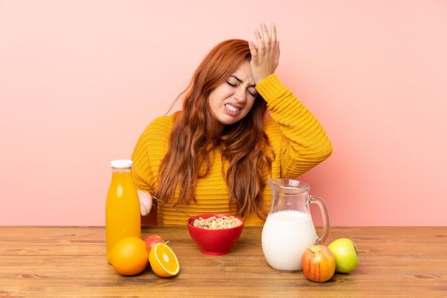 Рыжая девушка подростка завтракает в таблице, с сомнением выражение лица