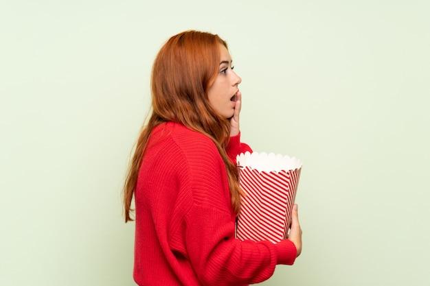 Рыжая девушка подросток с свитер над зеленой стеной, держа миску попкорна