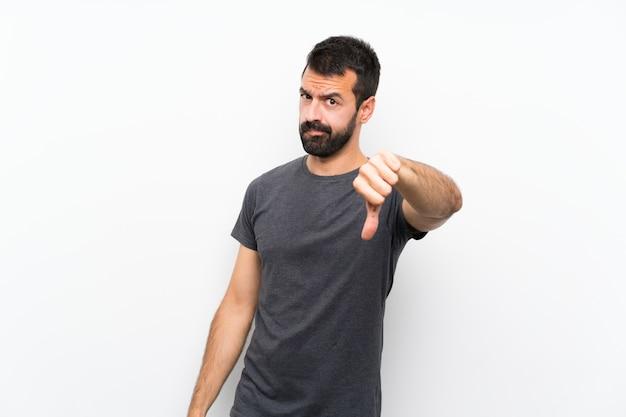 否定的な表現で親指を示す分離の白い壁の上の若いハンサムな男