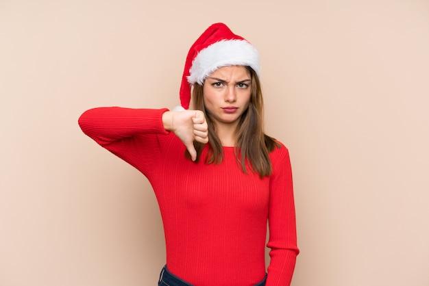 サインダウン親指を示す孤立した壁の上のクリスマス帽子の少女
